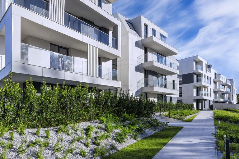 Walkway leading along the new modern white complex of apartment buildings