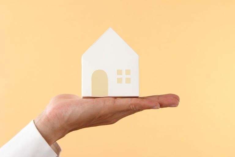 asian businessman holding model of house